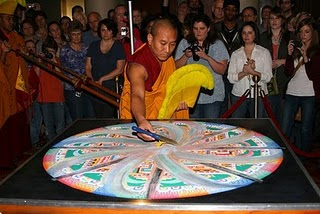 sweeping sand up of the mandala, circular and clockwise motion.